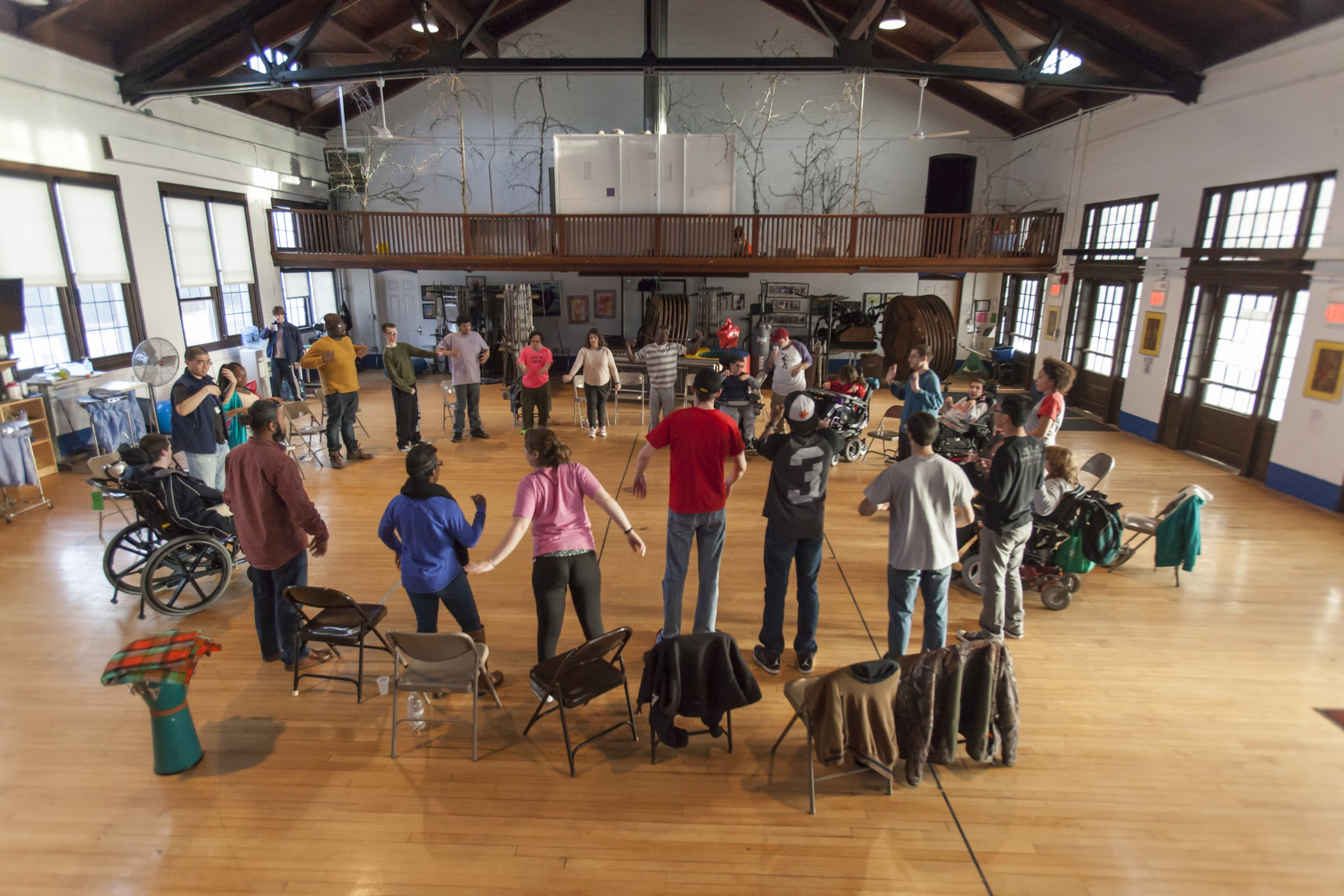 Group of young adults with various disabilities standing in a circle in a gym
