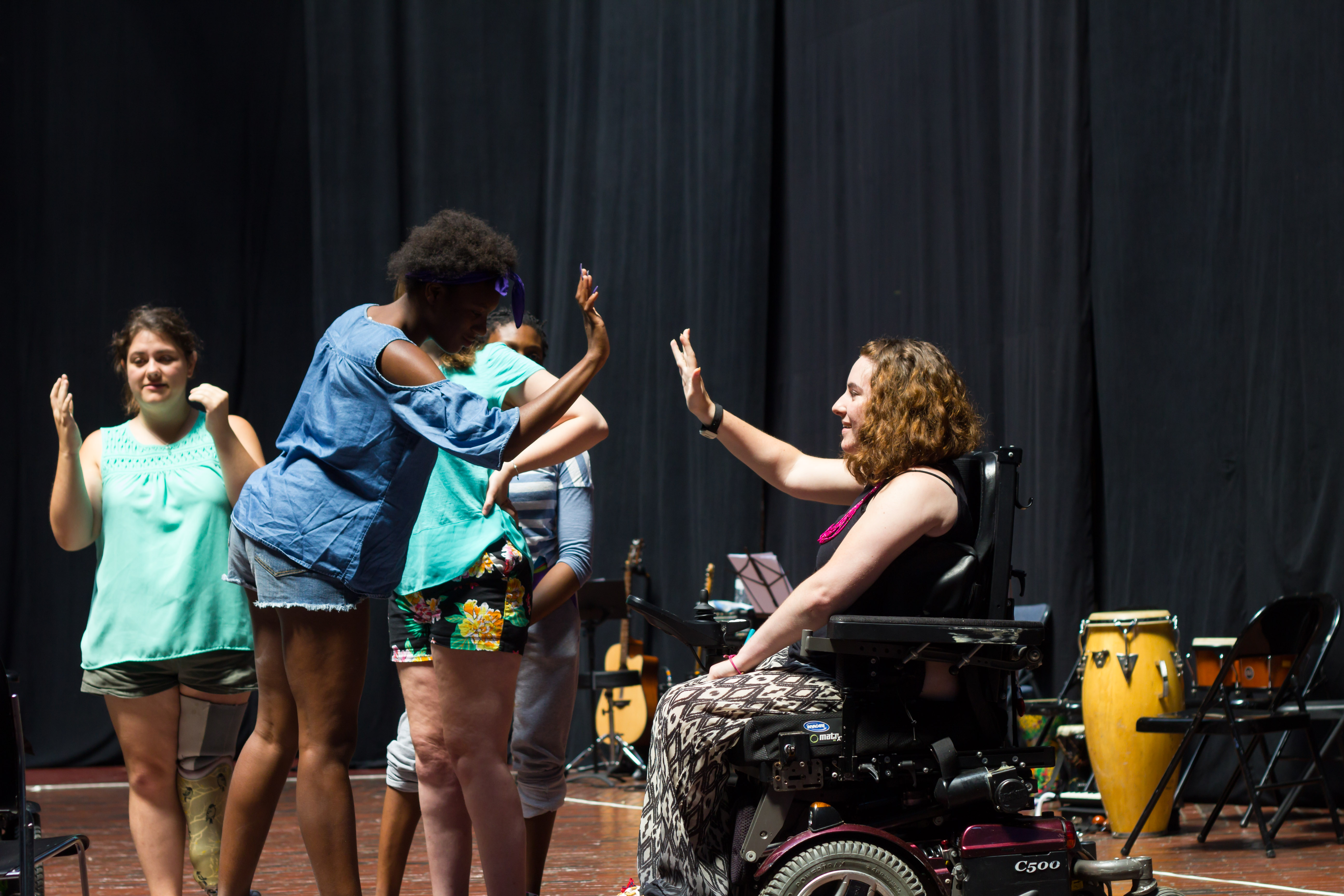 A young black woman and a young white woman in a wheelchair giving each other a high five