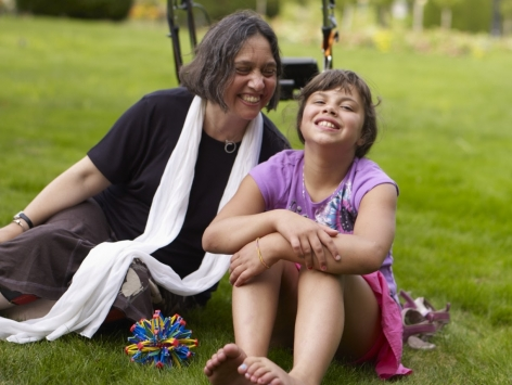 Young girl and a middle aged woman sits in grass field with a walker behind them
