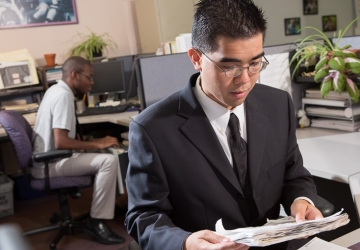 A young man in a suit works at a desk, while a co-worker files things behind him