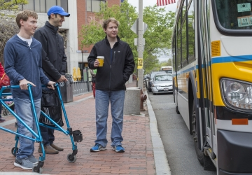 Three men wait on the sidewalk as a bus pulls up. One of them is using a walker.