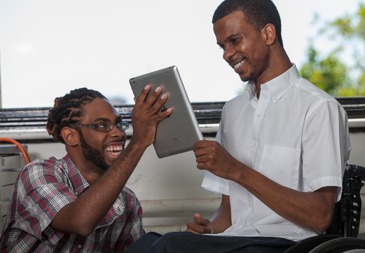 Two young black men looking at an iPad screen, smiling at what they see