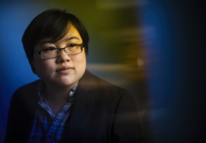 Photo: Headshot of Lydia Brown, young East Asian person, with short black hair, wearing glasses, a plaid shirt, and black jacket. They are looking in the distance, posed against a stylized blue dramatic background. Photo by Adam Glanzman.