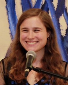 Allegra, a white woman with brown shoulder length hair, smiling for a picture
