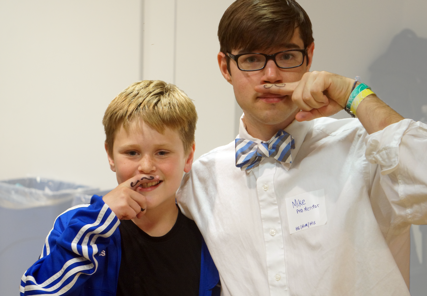 A young boy and his mentor make goofy faces at the camera