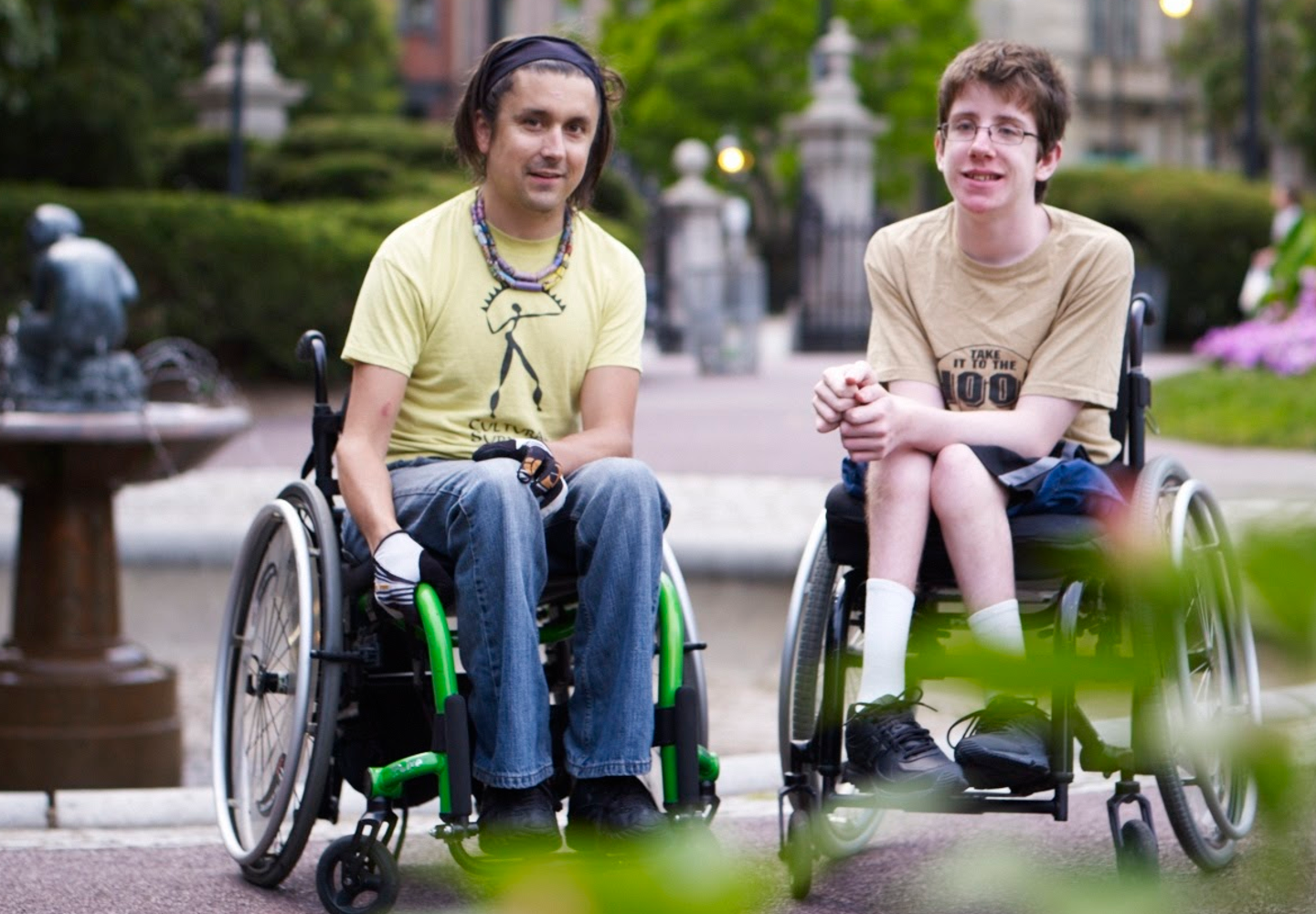 A young man in a wheelchair and a teenage boy in a wheelchair next to each other in the Boston Public Garden.