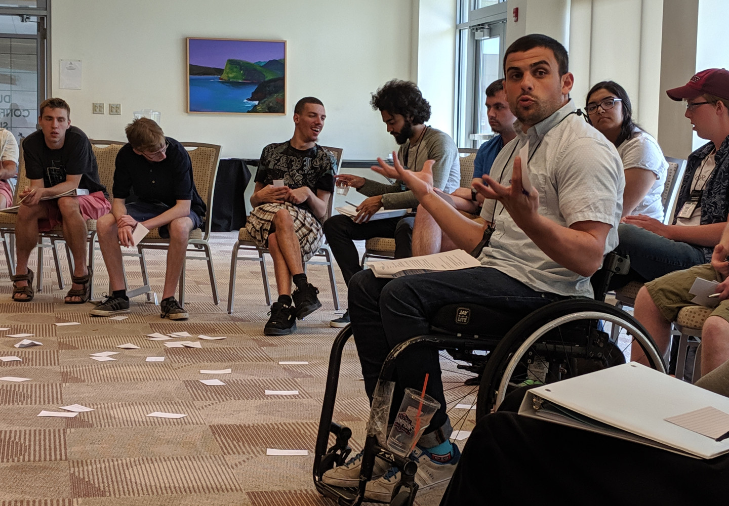 White man in a wheelchair leading a group exercise with a class