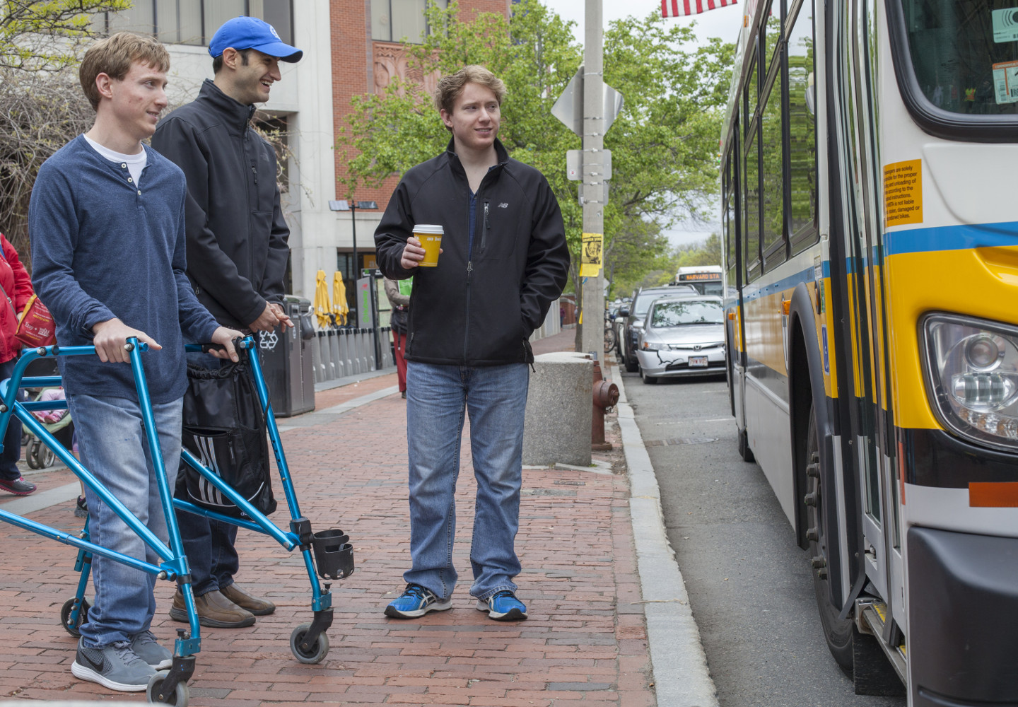 Young white man with a walker waiting for a bus with two friends