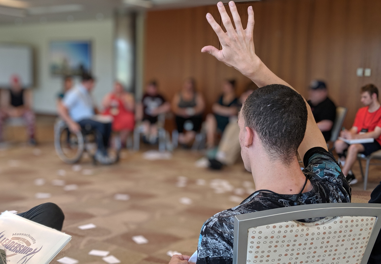 Young black man raises his hand to speak while sitting in a circle of his disabled peer