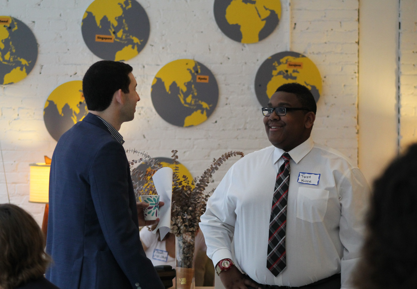 Young black man in a dress shirt and tie talks with a young white professional in a business coat