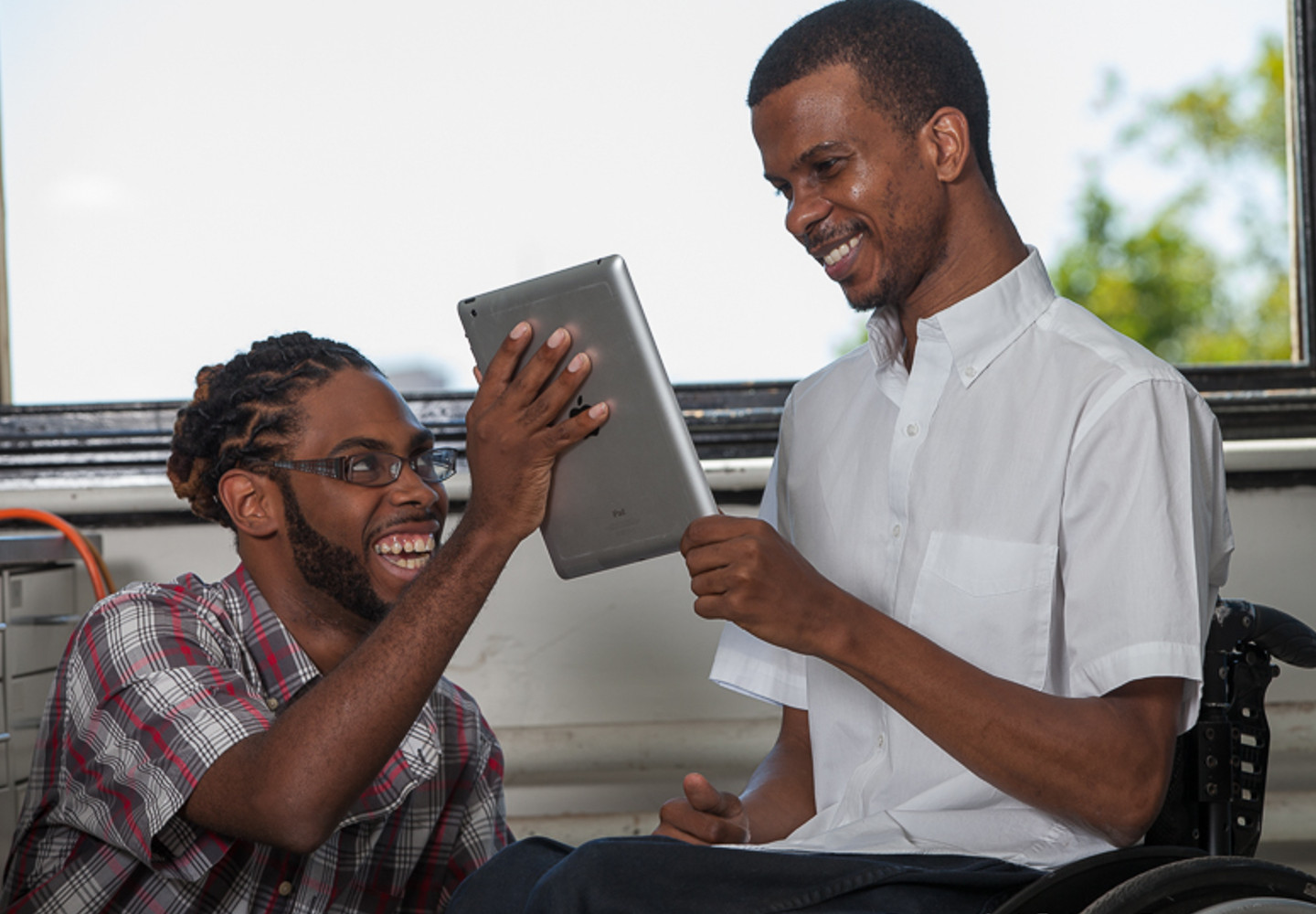 Young black man holds an iPad up for another young black man in a wheelchair