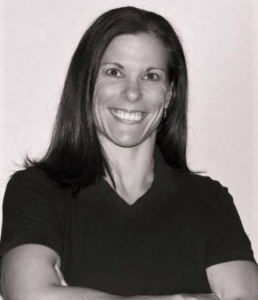 Black and white headshot of Amanda Kloo, a smiling woman with shoulder length dark hair, wearing a v-neck t-shirt.